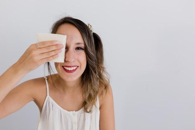 Fille enlève son maquillage avec un tampon en tissu avec les yeux ouverts
