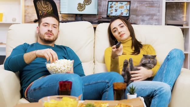 Une fille ennuyée assise sur le canapé avec le chat sur ses genoux et son petit ami à côté d'elle utilise la télécommande de la télévision.