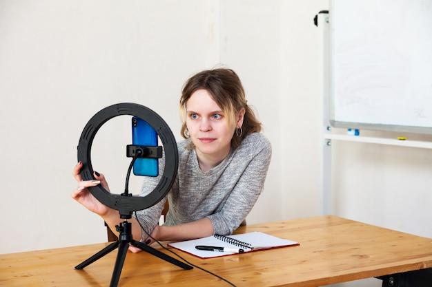 Fille enregistrant une vidéo sur smartphone et s'allumant avec une lampe annulaire