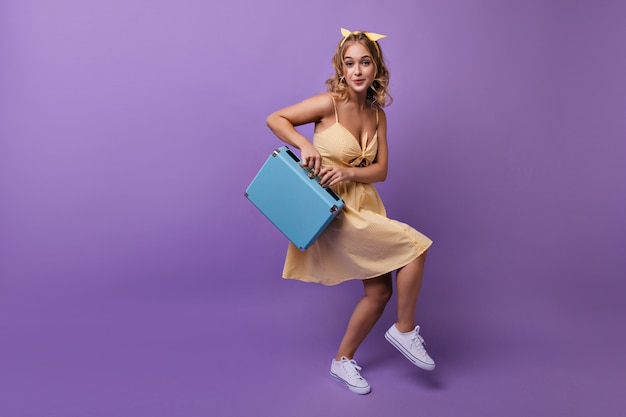 Fille enthousiaste avec une coiffure ondulée s'amusant avant le voyage. portrait de femme blonde insouciante dansant avec valise bleue.