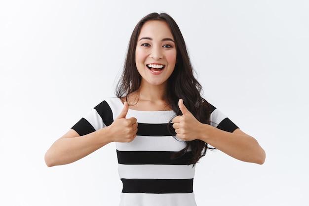 Une fille enthousiaste encourage son ami à suivre. jolie fille est-asiatique en t-shirt rayé montre le pouce levé et souriant excité, comme un plan génial, approuve une excellente idée, se tient sur fond blanc