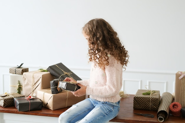 Fille entourée de coffrets cadeaux
