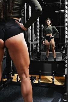 Une fille entraîne ses jambes dans la salle de sport avec une barre posant devant un miroir mode de vie sportif garder la motivation de remise en forme en forme