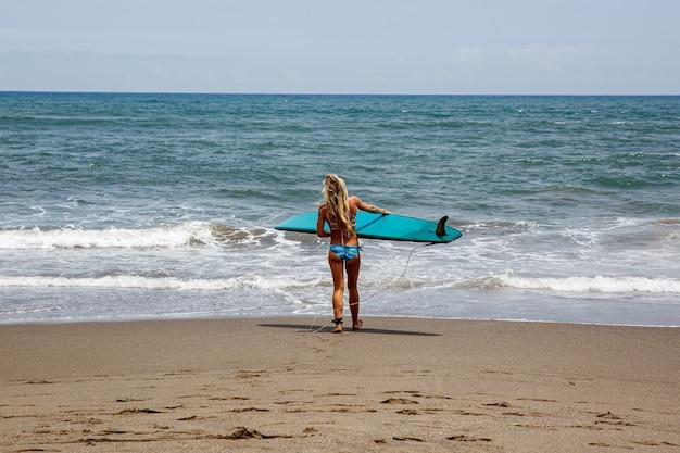Fille entre dans l'eau pour surfer.