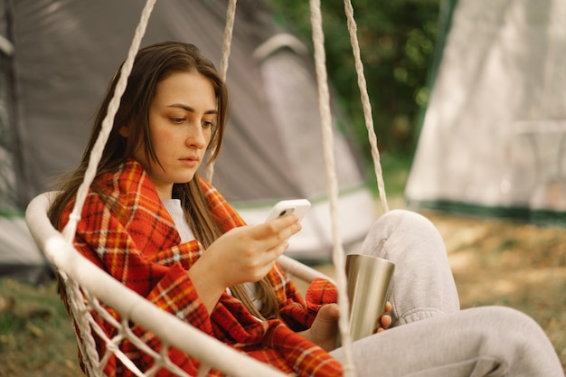 Fille enveloppée dans du thé à carreaux et utilisant un téléphone dans un fauteuil suspendu à l'extérieur, les gens utilisent la technologie