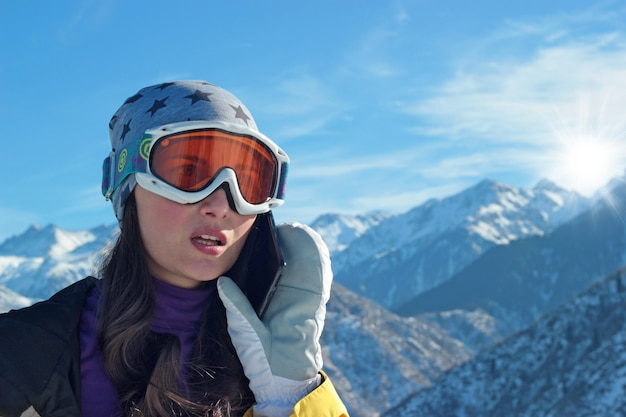 Une fille en équipement de ski avec une expression faciale anxieuse passe des appels téléphoniques.