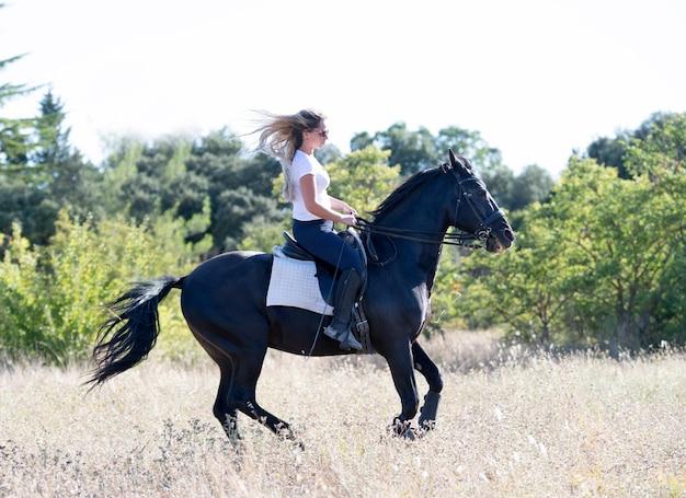 Fille d'équitation entraîne son cheval noir