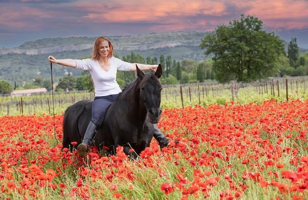 La fille d'équitation entraîne son cheval noir