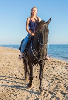 Fille d'équitation sur la plage