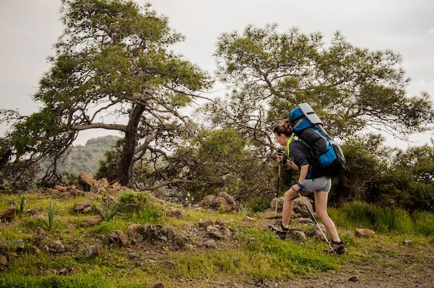Fille d'escalade sur le chemin avec sac à dos de randonnée