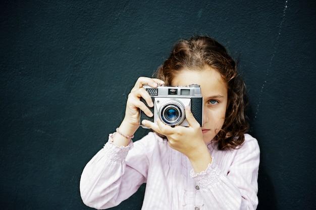 Fille espagnole aux cheveux bruns et aux yeux bleus en prenant une photo