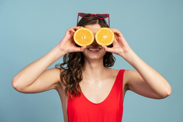 La fille espiègle couvre ses yeux avec deux moitiés d'une orange