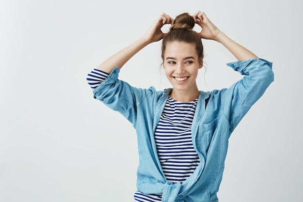 La fille essaie une nouvelle coiffure. projectile studio, de, joyeux, émotif, européen, girl, confection, chignon, sur, cheveux, et, regarder côté, miroir, sourire positivement, quoique, debout, dans, élégant, équipement