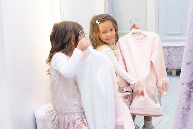 Fille essayant des vêtements dans une cabine d'essayage dans un magasin de vêtements.