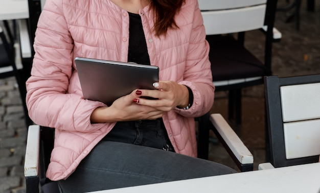 La fille est une adolescente dans ses mains tient une tablette. il regarde les réseaux sociaux.