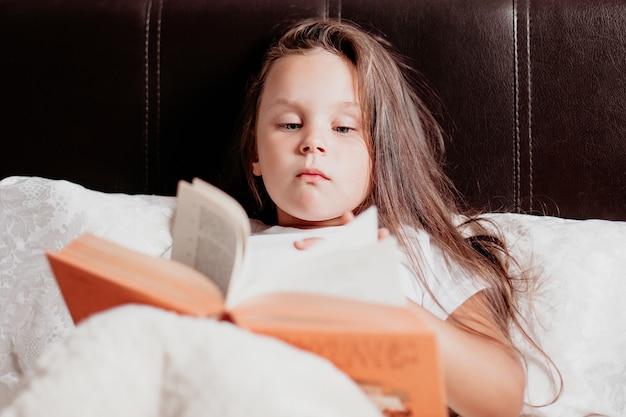 La fille est allongée sur un lit blanc et lit un livre orange, le confort de la maison et l'auto-éducation.