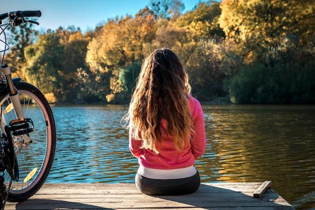 La fille est assise au bord de la rivière. vélo sur la rivière avec un sac sur le coffre