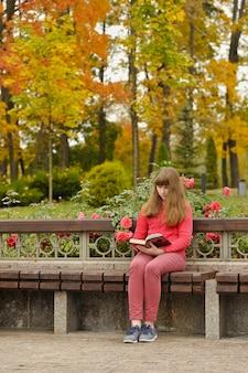 Fille est assise sur un banc et livre de lecture, automne.
