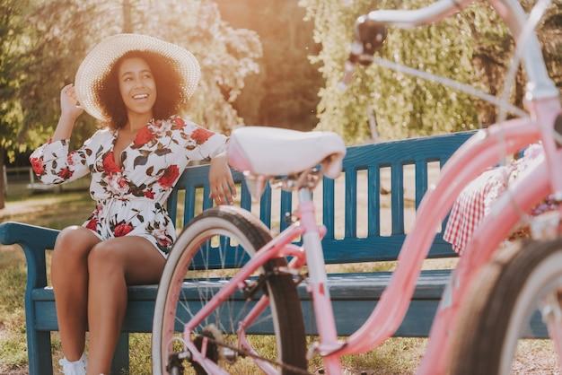 Fille est assise sur un banc de parc à côté de la bicyclette.