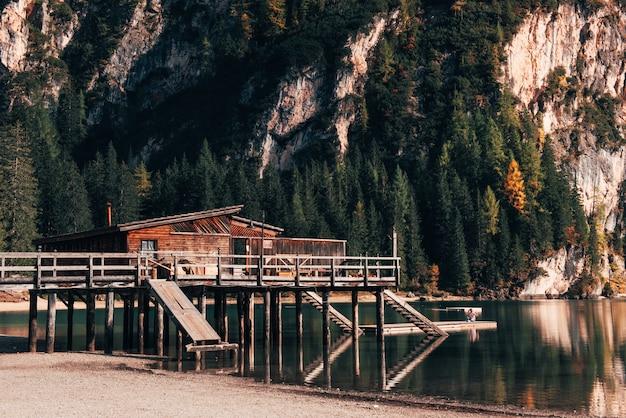 La fille est assise sur le bord de l'embarcadère et prend un selfie. lieu touristique avec bâtiment en bois et poire
