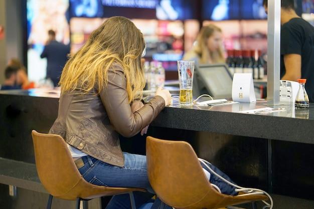 Une fille est assise à un comptoir de bar