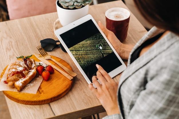 Une fille est assise dans un café et regarde une tablette, une fille dans un café sourit, planifie des choses. il y a des bonbons sur la table
