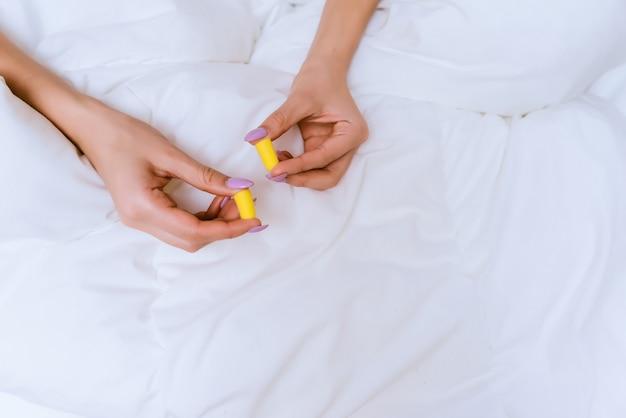 Une fille est assise dans son lit sous une couverture blanche, tient des bouchons d'oreille jaunes contre le bruit de la rue