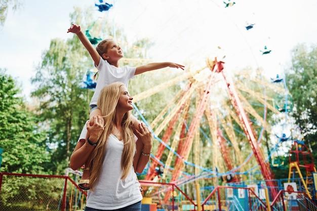 La fille est assise sur les épaules. joyeuse petite fille sa mère passe un bon moment dans le parc ensemble à proximité des attractions.
