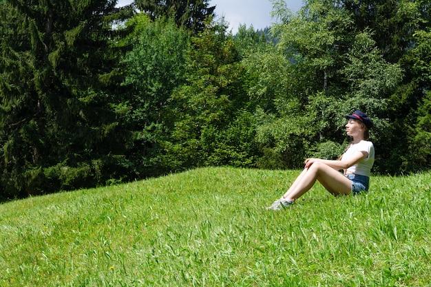 Une fille est assise sur un fond de montagnes sur la pelouse verte et profite du soleil.