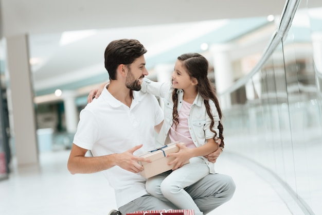 La fille est assise sur les genoux de son père près du magasin.