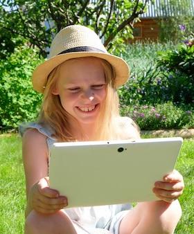 Une fille est assise sur l'herbe et tient une tablette dans ses mains