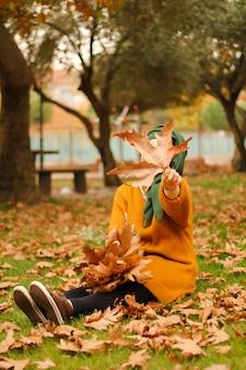 Fille est assise sur une pelouse dans le parc en automne tenant une énorme feuille