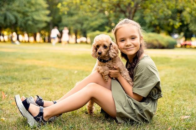 Fille est assise sur une pelouse verte avec un chien caniche.
