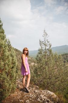 La fille est assise sur un rocher. le long de la rivière coule