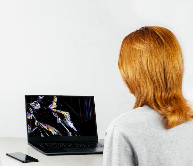 Fille est assise à une table et regarde un ordinateur portable avec un écran cassé et fissuré dans des taches colorées