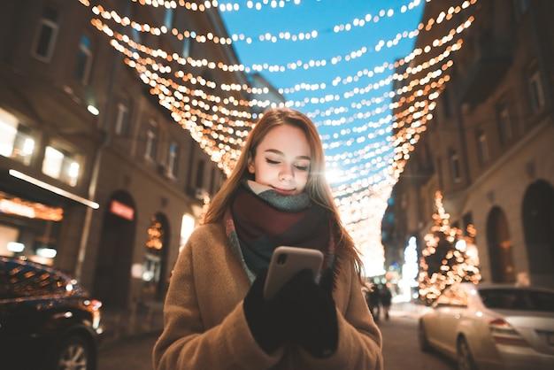 Fille est dans les vêtements chauds debout dans la rue et à l'aide d'un smartphone, fond de lampadaires
