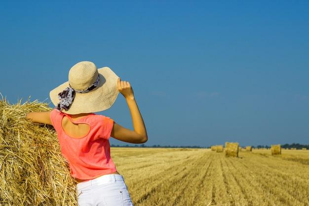 La fille est debout près d'une balle de paille et regarde au loin dans le champ