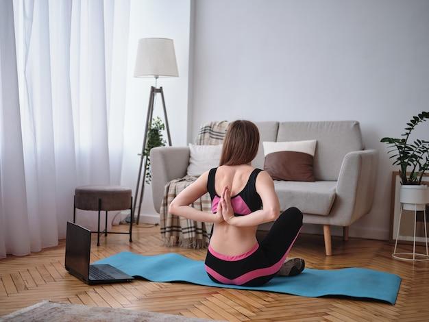 La fille est engagée dans le fitness à la maison. élongation