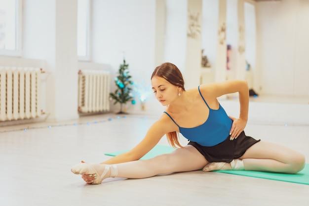 La fille est engagée dans la gymnastique, fait des étirements dans la salle de gym