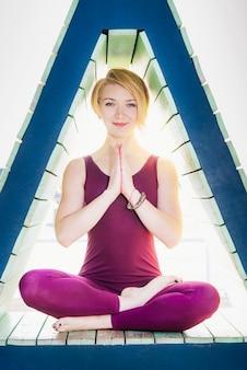 La fille est engagée dans le yoga dans une figure triangulaire