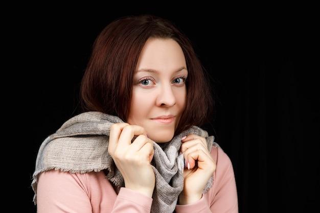 La fille est enveloppée dans une écharpe grise. portrait en gros plan.