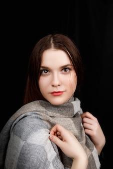 La fille est enveloppée dans une écharpe grise