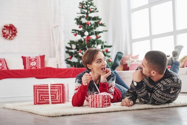 La fille est excitée quel genre de cadeau à l'intérieur de la boîte. belle jeune couple allongé sur le salon avec arbre de vacances vert à l'arrière-plan