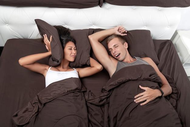 Fille est grandement tourmentée en essayant de dormir, mais le ronflement de son jeune homme ne permet pas cela