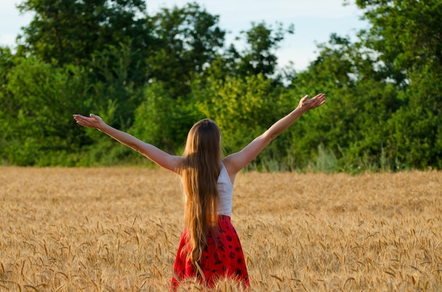 Fille est de retour dans un champ de blé avec ses bras levés vers le ciel