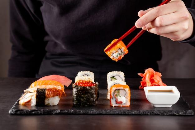 Une fille est titulaire d'une baguettes chinoises rouges et manger des sushis