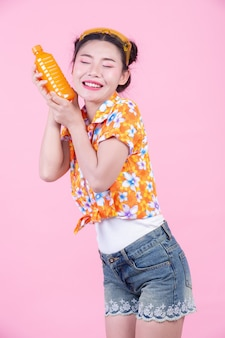 La fille est titulaire d'une bouteille de jus d'orange sur un fond rose.