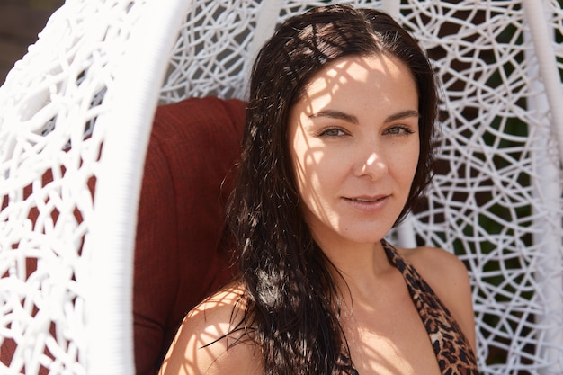 Fille d'été posant à l'extérieur dans une chaise de nid blanc. femme insouciante aux cheveux noirs se détendre dans un fauteuil à balançoire, jolie femme portant un maillot de bain élégant, dame brune