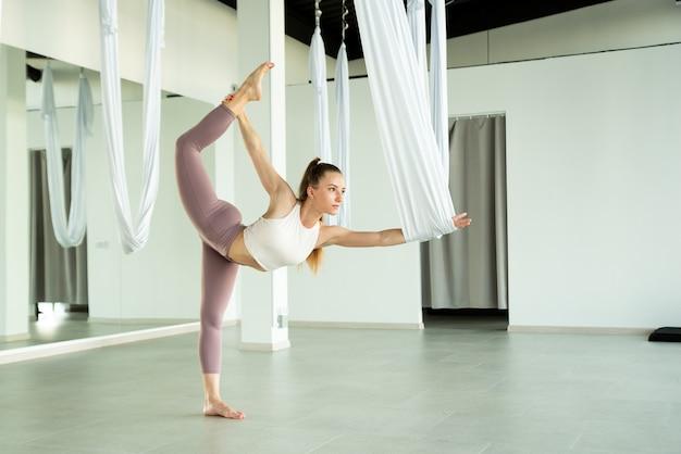 La fille étire sa jambe avec un hamac elle pratique le yoga de mouche