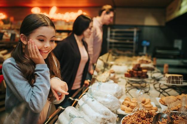 Fille étonnée debout sur une étagère avec des bonbons et en les regardant